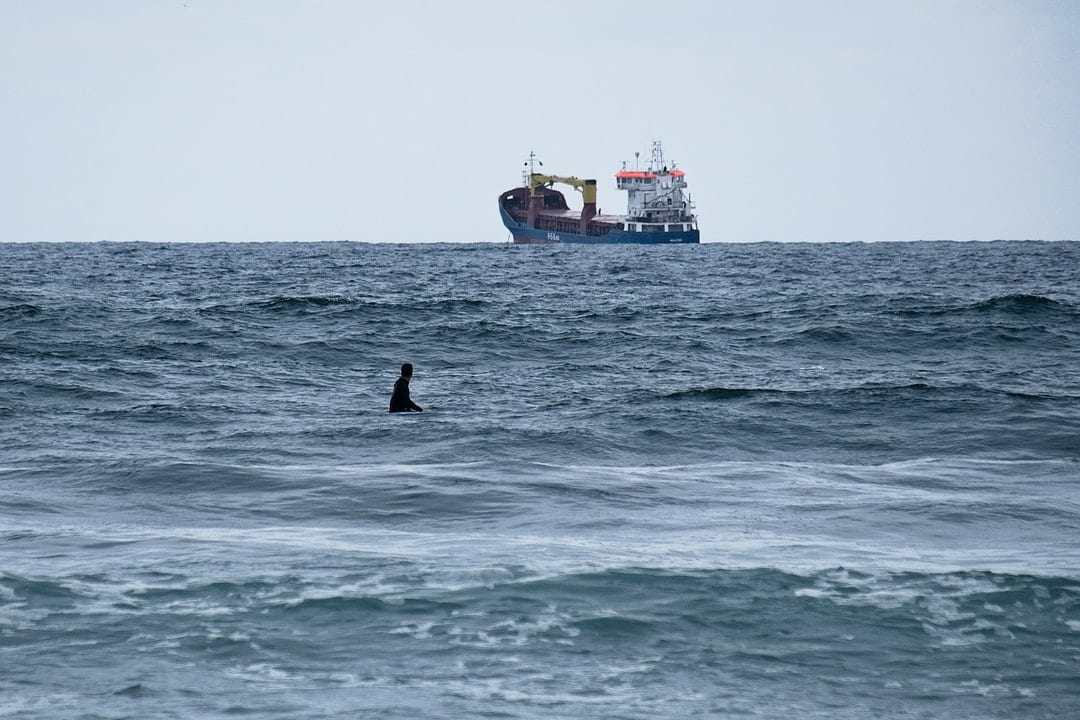 A man riding on the back of a boat in the ocean